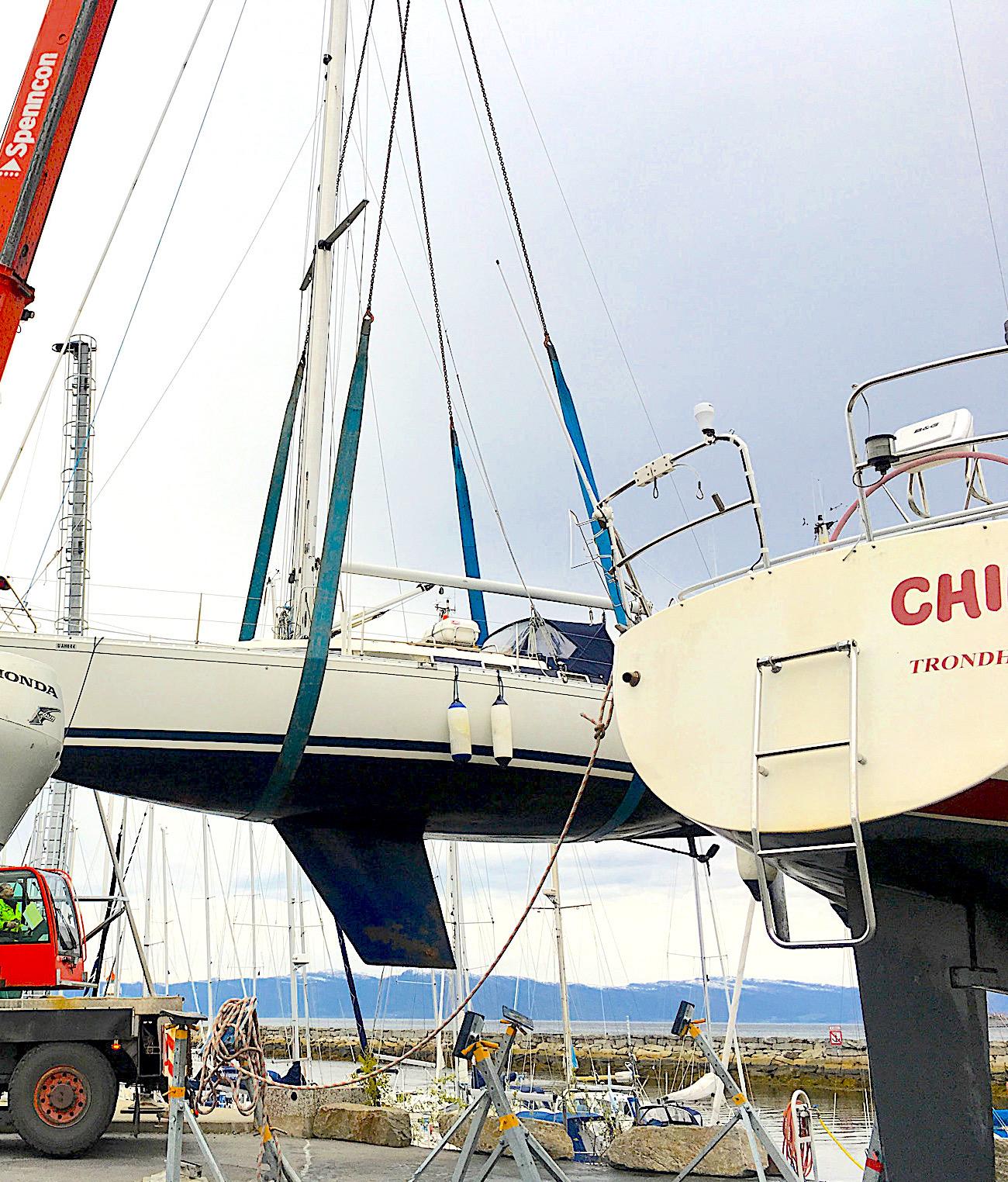 Kran løfter seilbåt i serviceområdet.